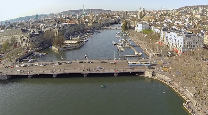 The skyline of Zurich with the Bellevue bridge in front and the Limmat and churches in the background.